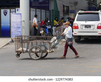 MAI SAI, THAILAND—MARCH 2018:  A woman pushes an empty cart on the road in Mai Sai, the last city in northern Thailand.