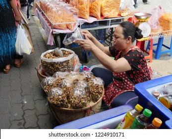 MAI SAI, THAILAND—MARCH 2018: A woman scoops walnuts for sale on the roadside in Mai Sai, the last city bordering Thailand and Myanmar.