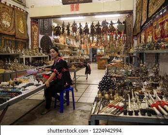 MAI SAI, THAILAND—MARCH 2018: A woman sits inside a store of arts and handicrafts in Mai Sai near the Thai-Burmese gate.
