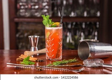 """""""Mai Tai"""" is an alcoholic cocktail based on rum. It stands on a wooden table surrounded by a shaker, a measuring glass, a strainer, bar spoons. Decorated with mint leaves and orange slice"""