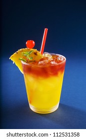 A mai tai cocktail garnished with pineapple and a cherry, studio shot