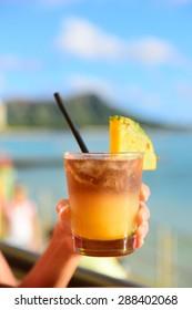 Mai Tai hawaiian drink on beach bar. Close up of alcoholic drink. Friends toasting having fun on Waikiki beach, Honolulu city, Oahu, Hawaii USA.