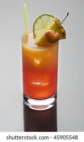 Mai Tai mixed drink with  fruit garnish on a plain grey background with reflection