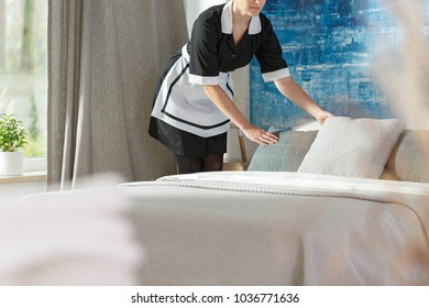 Maid in black uniform putting pillows on a hotel bed