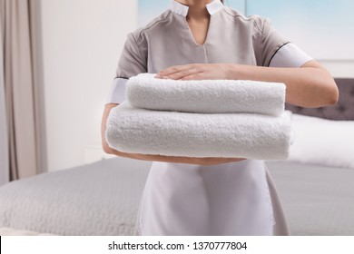 Maid with fresh towels in hotel room, closeup