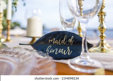Maid of honour leaf place card for a Romantic Wedding Table Top Layout Table Spread no people no human tropical location with gold cutlery and scenic view