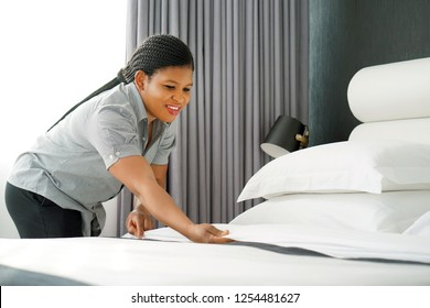 Maid making bed in hotel room. Staff Maid Making Bed. African housekeeper making bed.