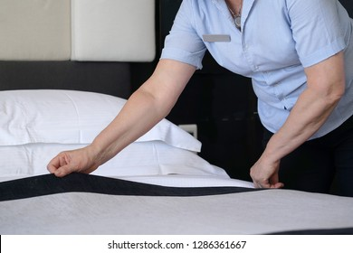 Maid making bed in hotel room. Housekeeper Making Bed