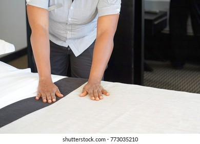 Maid making bed in hotel room.