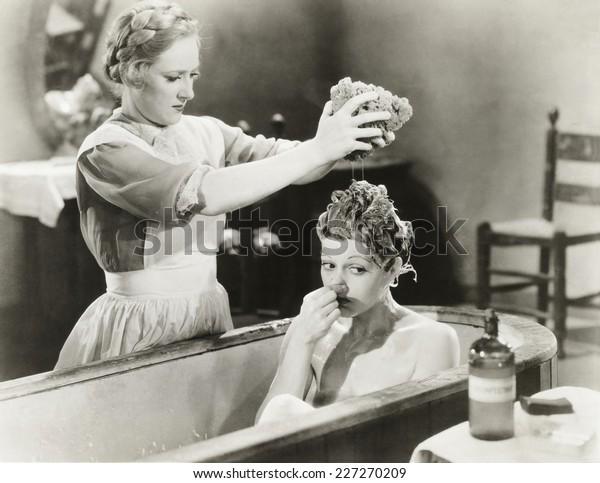 Maid squeezing sponge on woman in bathtub