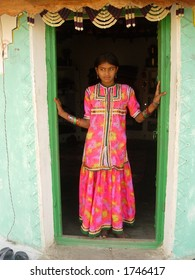 a maiden posing on the door of a home in a village in india