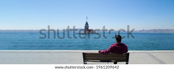 Maiden tower background, Vacation and travel to istanbul. Man relaxes on bench looking over bosphorus and enjoying Maiden Tower view. Maiden Tower is best of Popular destinations in Turkey, istanbul.