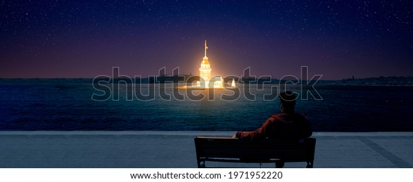 Maiden Tower shining burning like a lamp in night. Man relaxes on bench over bosphorus, enjoying view. Maiden Tower is best of Popular destinations in Turkey, istanbul. Abstract manipulated image