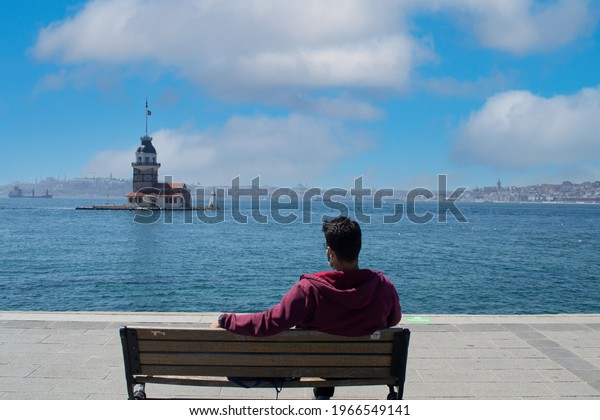 Maiden tower, Vacation and travel to istanbul. Man relaxes on bench looking over bosphorus and enjoying Maiden Tower view. Maiden Tower is best of Popular destinations in Turkey, istanbul.