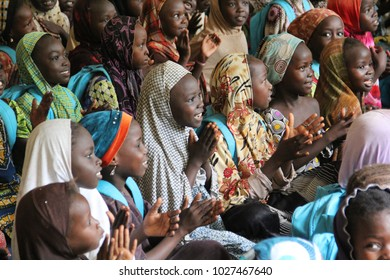 MAIDUGURI, NIGERIA - September 14, 2015: A group of young Nigerian girls smile and clap during class at a camp for internally displaced persons due to insecurity by the militant group Boko Haram