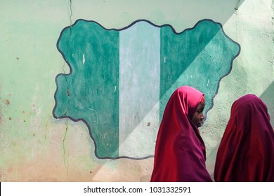 MAIDUGURI, NIGERIA - September 9, 2015: Girl students pass a classroom with the map and flag of Nigeria painted on it, at Success Private School, one of the first schools attacked by Boko Haram in '09