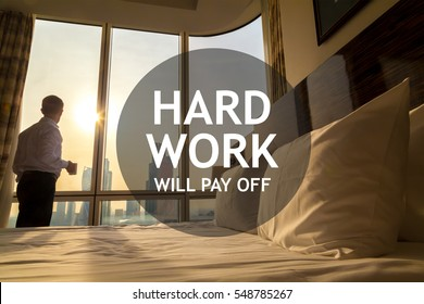 """Maid-up bed in cozy room. Young businessman with coffee cup standing at window looking at city scenery on the background. Motivational text """"Hard work will pay off"""""""