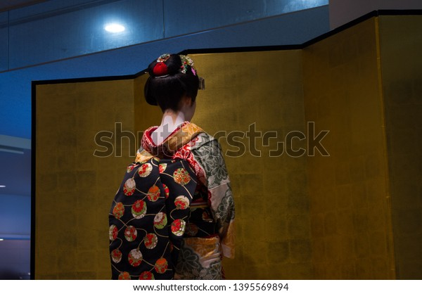 Maiko, an apprentice geisha in Kyoto and Western Japan, performing traditional Japanese dance in front of a golden screen