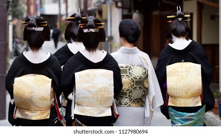 Maiko and Geisha walking around Gion in Kyoto Japan wearing traditional clothing with amazing makeup and hair.