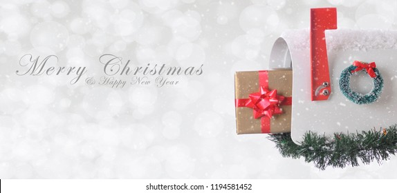 Mail Box with Christmas present with Merry Christmas and Happy New Year on a silver bokeh background with snow effect.