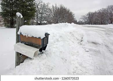 A mail box is nearly buried in deep snow after a snow plow cleared a rural road.