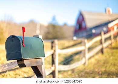 mail box with raised mailbox flag outside. american mailbox. rural view, blurred background