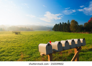 Mail boxes and an antique farm implement in a farming landscape, Stowe Vermont, USA