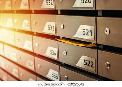 Mail boxes filled of leaflets and letters. Shallow DOF,Mailboxes and Lock in Rows at Entrance.