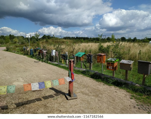 mail boxes lined up alongside a dirt road in countryside.