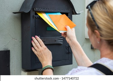 Mail carrier is inserting letters into mailbox. Woman is holding colorful envelopes. Postal worker delivering correspondence