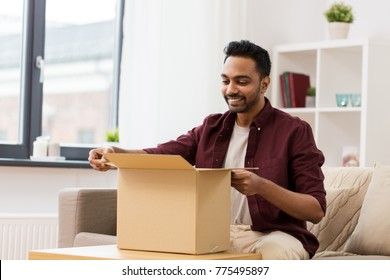 mail delivery, shipment and people concept - happy man opening parcel box at home