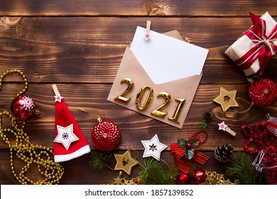 Mail envelope of craft paper with white sheet for text on wooden background with Christmas decor and Golden numbers 2021. letter to Santa Claus, wish list, new year's dream, gift. Flat lay, copyspace