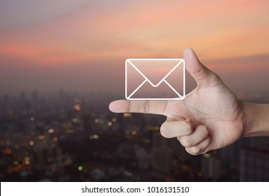 Mail icon on finger over blur of cityscape on warm light sundown, Contact us concept