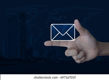 Mail icon on finger over world map and modern city tower, Contact us concept, Elements of this image furnished by NASA