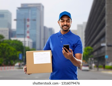 mail service, technology and shipment concept - happy indian delivery man with smartphone and parcel box in blue uniform over tokio city background
