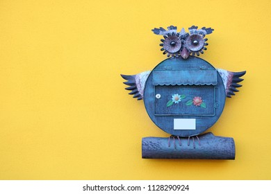 Mailbox in the form of an owl. Owl on a yellow background