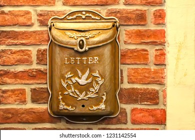 Mailbox (Letterbox). Beautiful vintage mailbox on a vintage brick wall. Iron Mailbox depicting a dove with a letter and ornament