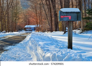 A mailbox at the side of a driveway after a snow storm
