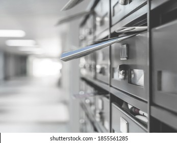 Mailboxes in the condominium. Mailboxes filled. Mail boxes filled of leaflets and letters. Defocused blurry background.