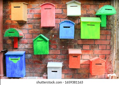 Mailboxes of different colors on a brick wall