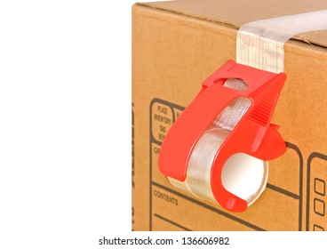 Mailing tape and box. Close up of brown cardboard box and red adhesive tape roll dispenser. Isolated on a white background. Copy space, room for text.