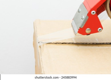 Mailing tape and box. Close up of brown cardboard box and red adhesive tape roll dispenser