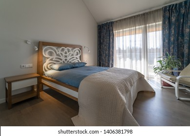 Main bedroom with big original bed, bedside tables, lamps on the wall, white armchair and flower pot near the window with curtains in the modern house