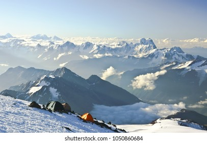 Main Caucasus and mt. Ushba  from mt. Elbrus south side and climbers tents at Pastukhov rocks at the sunrise.