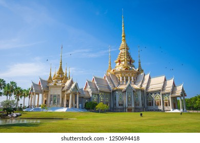 The main church of Wat Non Kum or Non Kum temple, Famous temple of Nakhon Ratchasima, Thailand with the flying bird on the roof, green lawn in the front and have bright blue sky in the background