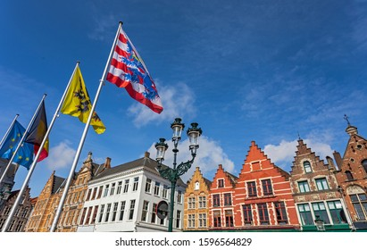 Main city square in Bruges with flags and traditional architecture. Row of colorful building in Bruges.