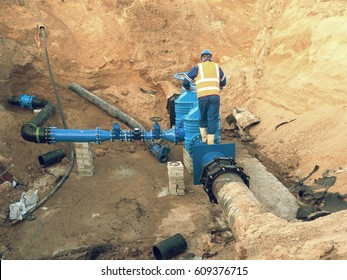 Main City water supply pipeline. Technical staff in reflective vest underground drive pipe gate.  Repaired pipeline system. Final check of repaired piping before covering by clay.