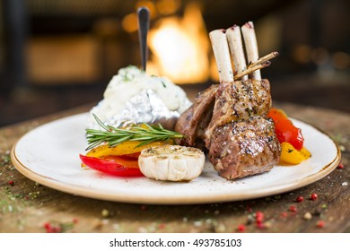 Main course dinner dish of roasted and grilled lamb ribs with green and red bell pepper, garlic and mashed potatoes. Restaurant food