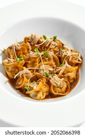 Main course in italian cuisine - meat tortellini with demi-glace sauce and mushroom cream. Beef ravioli on white plate. Tortellini with minced veal in beef sauce. Gourmet cuisine in restaurant menu
