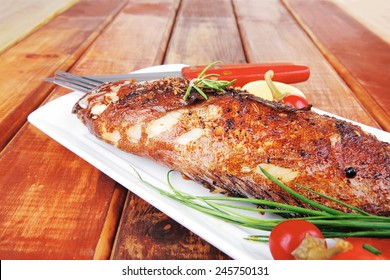 main course on wood: whole fryed sunfish on plate with lemons and peppers